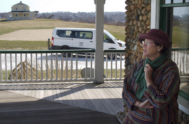 "In this Tuesday, April 11, 2017 photo, Fran Migliaccio, owner of Mig's Rig Taxi, stands on the porch near her taxi in New Shoreham, R.I., on Block Island. Migliaccio said she doesn't want to ban Uber and Lyft from the island, but thinks that everyone should be ""subject to the same level of scrutiny"" as everyone else on the taxi waitlist. (AP Photo/Matt O'Brien)"