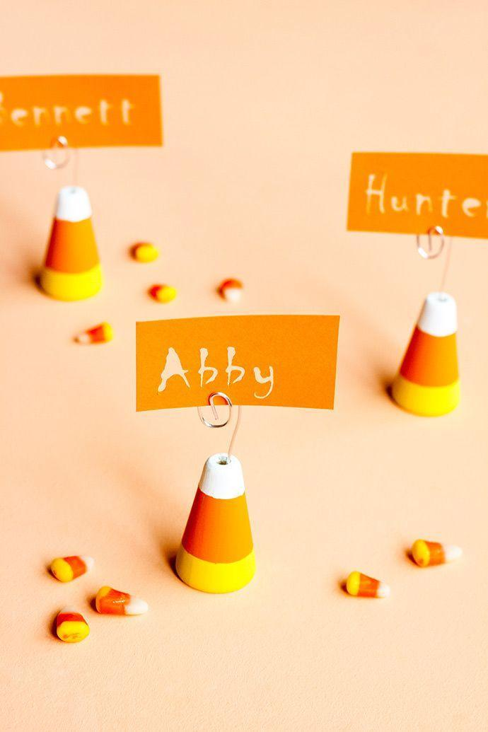 """<p>Just in time for your sit-down dinner on All Hallows' Eve, DIY these adorable candy corn place card holders. And in the days leading up to your holiday feast, you can use them to display photos on a shelf, mantel, or desk. </p><p><em><a href=""""https://www.handmadecharlotte.com/candy-corn-place-card-holders/"""" rel=""""nofollow noopener"""" target=""""_blank"""" data-ylk=""""slk:Get the tutorial at Handmade Charlotte »"""" class=""""link rapid-noclick-resp"""">Get the tutorial at Handmade Charlotte »</a></em></p>"""