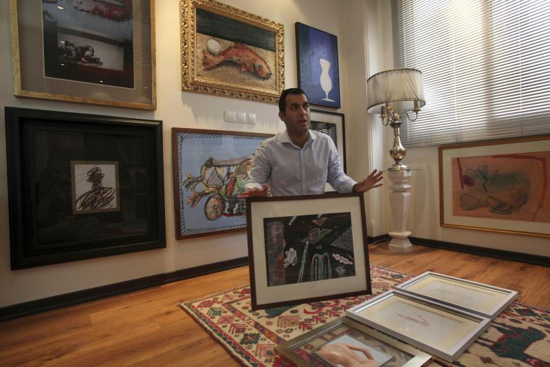In this Thursday, July 11, 2013 photo, Iranian art collector Ali Bakhtiari speaks about an artwork at his house, in Tehran, Iran. (AP Photo/Vahid Salemi)