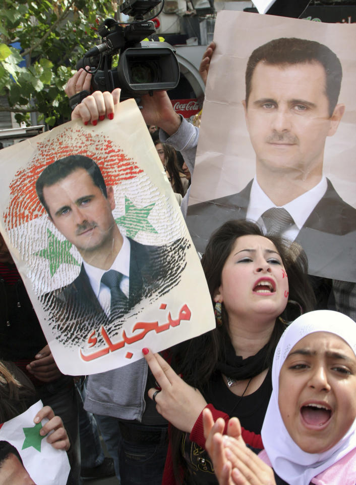 Pro-Syrian regime protesters, shout slogans and hold portraits of Syrian President Bashar Assad, during a demonstration against the Arab League decision to suspend Syria, in Damascus, Syria, on Sunday Nov. 13, 2011. Tens of thousands of pro-regime demonstrators gathered in a Damascus square Sunday to protest the Arab League's vote to suspend Syria over its bloody crackdown on the country's eight-month-old uprising. Saturday's Arab League decision was a sharp rebuke to a regime that prides itself as a bastion of Arab nationalism, but it was unlikely to immediately end a wave of violence that the U.N. estimates has killed more than 3,500 people since mid-March. (AP Photo/Bassem Tellawi)
