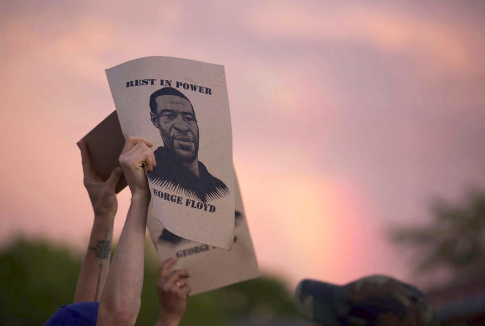 A protester holds a sign with an image of George Floyd during protests on May 27, 2020, in Minneapolis. (Christine T. Nguyen / Minnesota Public Radio via AP file)