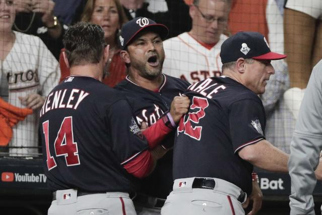 Washington Nationals manager Dave Martinez has to be restrained after being ejected for arguing an interference call during the seventh inning of Game 6 of the World Series. (AP Photo/David J. Phillip)