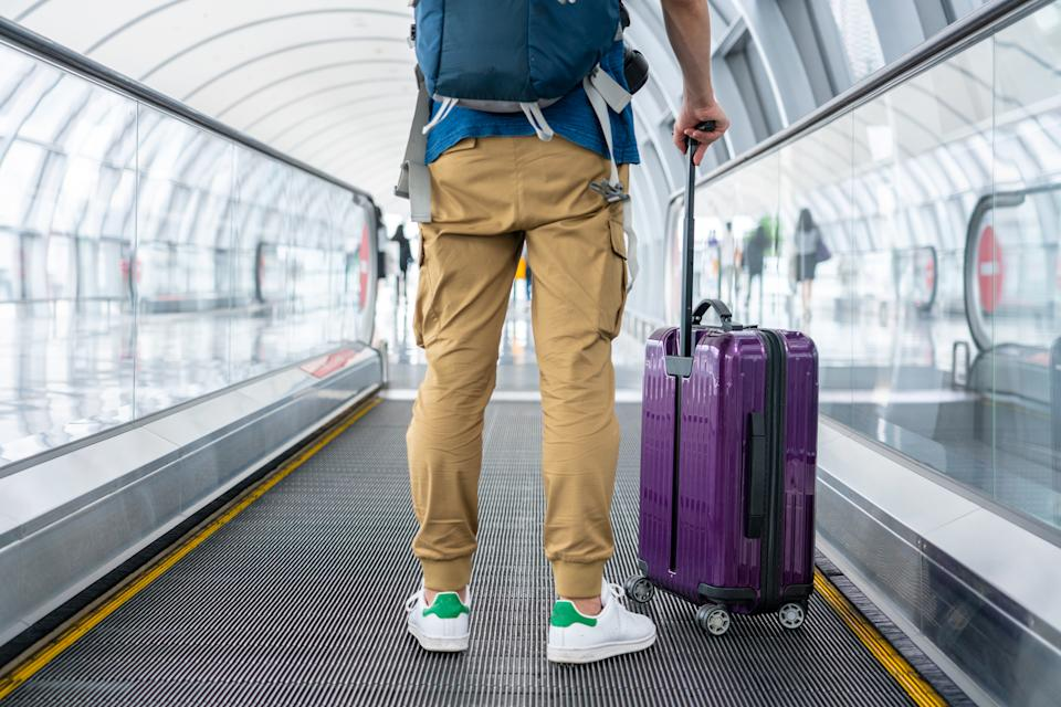 A Traveler walking on moving walkway in the airport