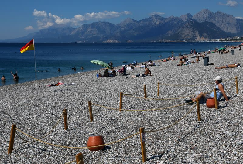 FILE PHOTO: A man sits in an area marked by cordons of ropes and wooden stakes to enforce social distancing measures on the Konyaalti beach in Antalya