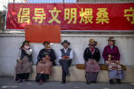 Members of the Buddhist faithful sit near a local holy site beneath a propaganda banner urging people to engage in a civilized manner in the Tibetan Buddhist practice of ritually burning pine branches in Lhasa in western China's Tibet Autonomous Region, Thursday, June 3, 2021, as seen during a government organized visit for foreign journalists. High-pressure tactics employed by China's ruling Communist Party appear to be finding success in separating Tibetans from their traditional Buddhist culture and the influence of the Dalai Lama. (AP Photo/Mark Schiefelbein)