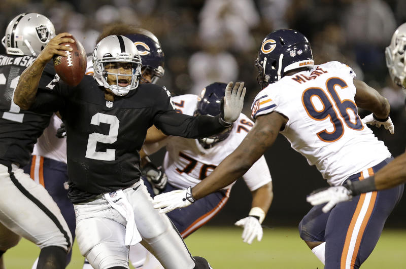 Oakland Raiders quarterback Terrelle Pryor (2) avoids Chicago Bears defensive end Kyle Moore (96) on his 25-yard touchdown run during the third quarter of an NFL preseason football game in Oakland, Calif., Friday, Aug. 23, 2013. (AP Photo/Marcio Jose Sanchez)