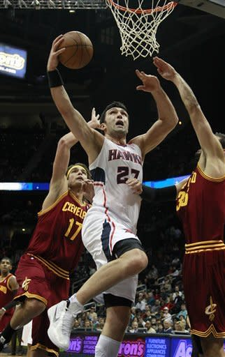 Atlanta Hawks center Zaza Pachulia (27) drives between Cleveland Cavaliers' Anderson Varejao (17) and Cleveland Omri Casspi, right, in the first half of an NBA basketball game on Saturday, Jan. 21, 2012, in Atlanta. (AP Photo/John Bazemore)