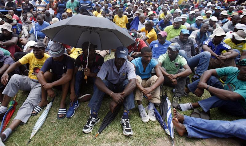 Mine workers sit on the grass while being addressed by their leaders outside the Lonmin platinum mine in Marikana near Rustenburg, South Africa, Thursday, Jan. 23, 2014. Workers of the Allied Metal and Construction Workers Union (AMCU) at Lonmin in Marikana, Anglo American Platinum (Amplats) and Impala mines started a strike on Thursday pushing for an entry-level monthly salary of 12,500 rand ($1,147 US). (AP Photo/Themba Hadebe)