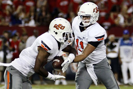 Oklahoma State quarterback Wes Lunt (11) hands off to running back Joseph Randle, left, against Arizona during the first half of an NCAA college football game at Arizona Stadium in Tucson, Ariz., Saturday, Sept. 8, 2012. (AP Photo/Wily Low)
