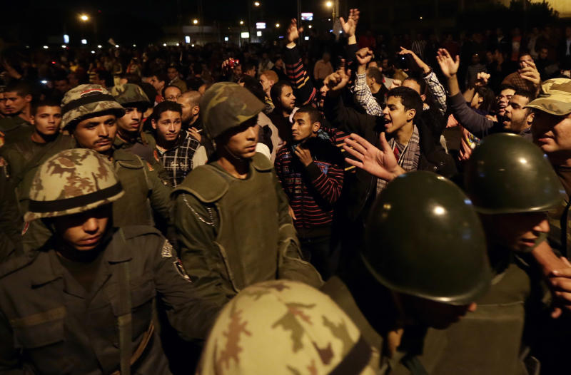 Egyptian protesters salute Egyptian army soldiers as they leave their position outside the presidential palace, in Cairo, Egypt, Friday, Dec. 7, 2012. Egyptian protesters broke through a barbed wire barricade that was keeping them from getting closer to the presidential palace. Egypt's political crisis spiraled deeper into bitterness and recrimination Friday as thousands of Islamist backers of the president vowed vengeance at a funeral for men killed in bloody clashes earlier this week and large crowds of the president's opponents marched on his palace to increase pressure after he rejected their demands.(AP Photo/Hassan Ammar)