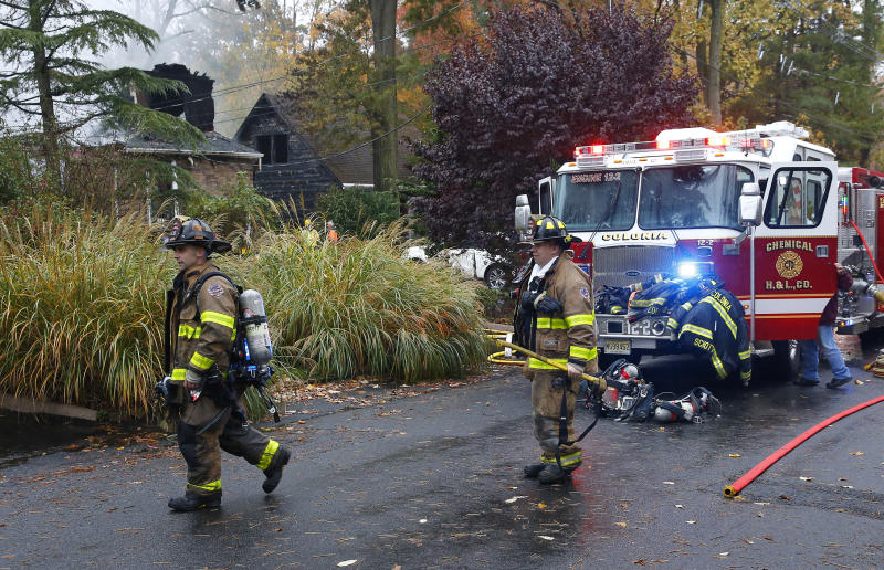Woodbridge firefighters work the scene of fire after a plane crashed into a home located at 84 Berkeley Ave. Tuesday, Oct. 29, 2019, in Woodbridge,N.J. (AP Photo/Noah K. Murray)