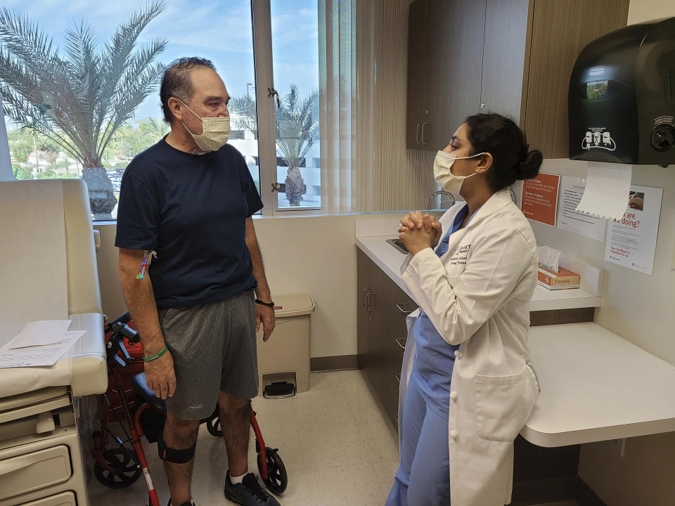 In this photo provided by Dignity Health St. Joseph's Hospital, Arthur Sanchez, left, speaks with Dr. Ashwini Arjuna during a follow-up appointment, post-transplant, at St. Joseph's Hospital in Phoenix, Wednesday, Oct. 21, 2020. Seven months after he was first hospitalized in his hometown of Las Cruces, New Mexico, with COVID-19, the 52-year-old utility worker has a brand new set of lungs. (Courtesy of Dignity Health St. Joseph's Hospital via AP)