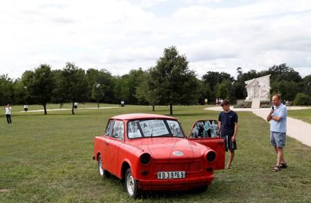 People stand next to Trabant, an East German car, at the Pan-European Picnic Memorial Park in Sopronkohida