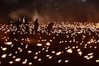 <p>Volunteers help to light first thousands of flames in the dry moat of the Tower of London as part of an installation called Beyond the Deepening Shadow: The Tower Remembers, to mark the centenary of the end of First World War. (Picture: PA) </p>