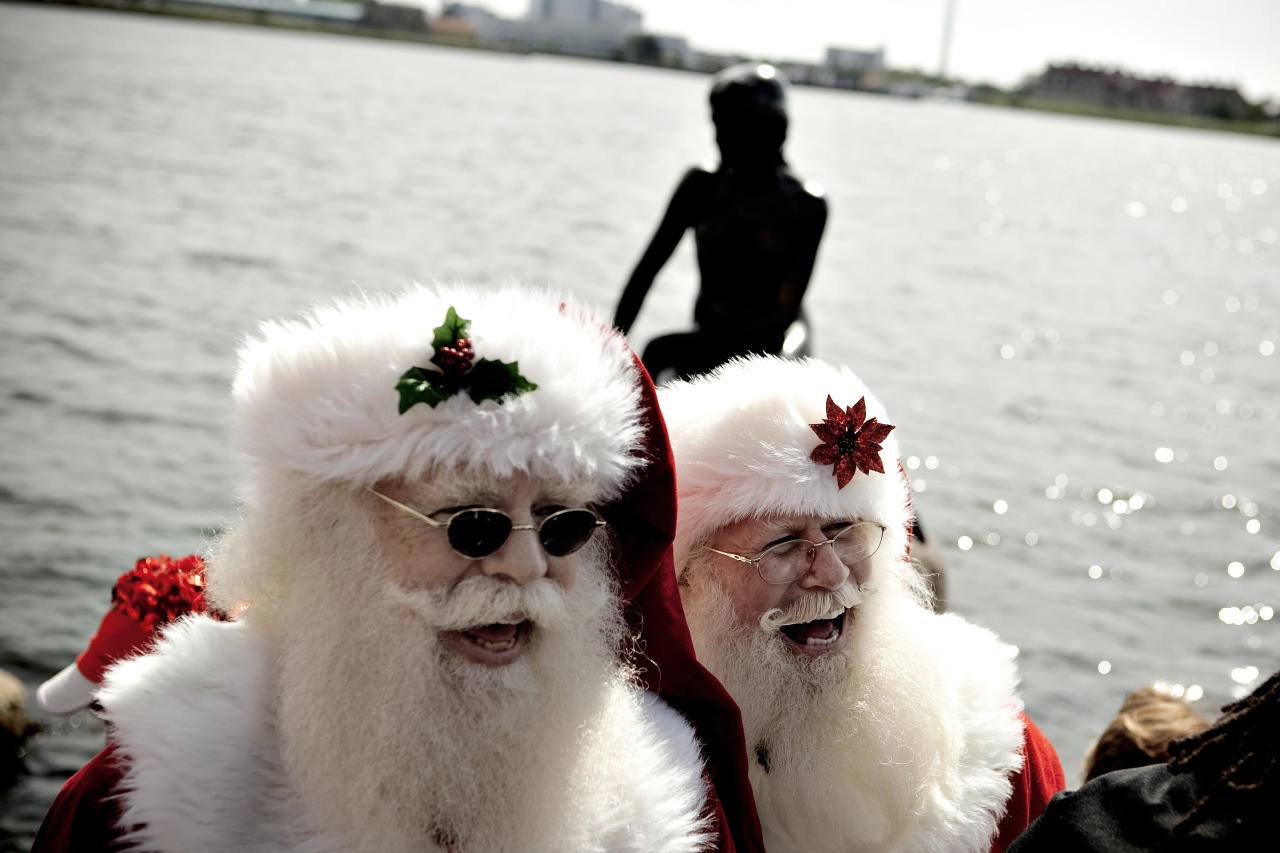 Participants laugh during the World Santa Claus Congress next to The Little Mermaid statue in the harbour of Copenhagen, on Monday, July 18, 2011. The World Santa Claus Congress has taken place in the Dyrehavsbakken amusement park (usually shortened to Bakken) north of Copenhagen since 1957. (AP Photo/POLFOTO, Joachim Adrian) DENMARK OUT