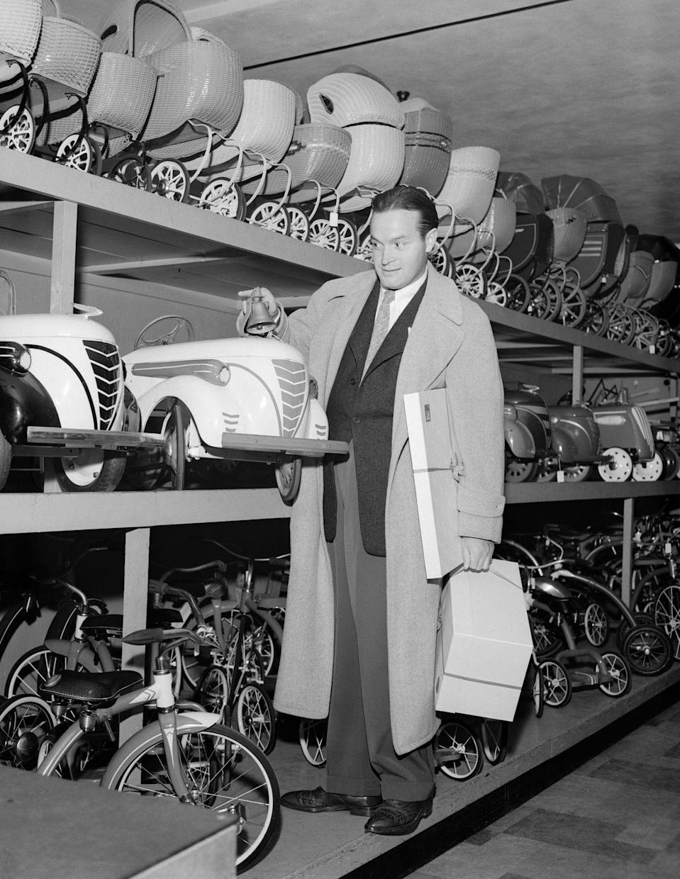 <p>Bob Hope visited a Los Angeles department store to pick out presents for his children, Donna and Tony. The comedian looks like he's still dressed for work with a suit and tie under his overcoat.</p>