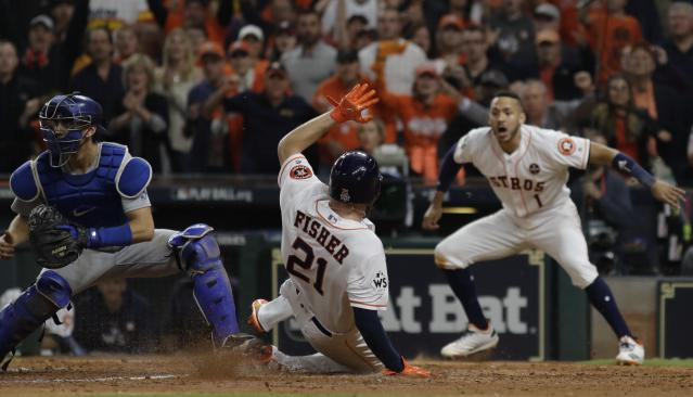 The Astros' Derek Fisher scores on a hit by Alex Bregman during the 10th inning of Game 5. (AP)