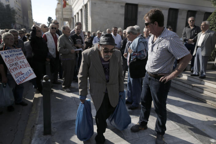 An elderly man carries bags with food as he walks through a rally by protesting pensioners in central Athens, on Thursday, Oct. 31, 2013. Elderly Greeks have faced successive pension cuts since Greece began relying on international rescue loans in 2010, and have also been hard hit by health care cuts.(AP Photo/Petros Giannakouris)