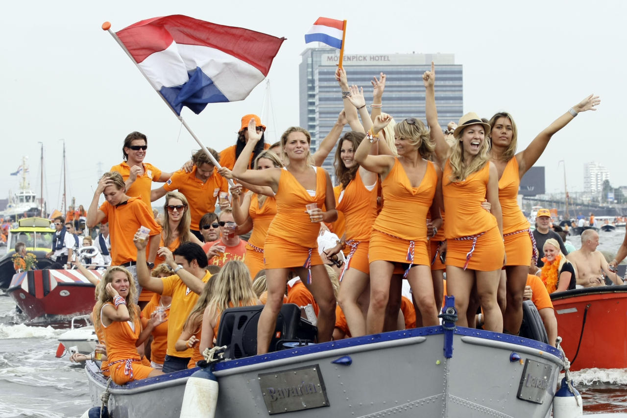 Women dance on a boat wearing orange minidresses from brewer Bavaria during the Dutch national soccer team's parade through the canal system of downtown Amsterdam, Netherlands, Tuesday, July 13, 2010. Bavaria made headlines at the World Cup when about 30 women dressed in the dresses danced at the Netherlands-Denmark match in what was called an ambush marketing stunt. (AP Photo/Vincent Jannink)