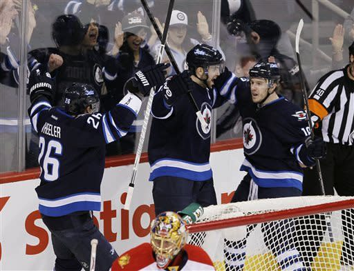 Winnipeg Jets' Andrew Ladd (16), Bryan Little (18) and Blake Wheeler (26) celebrate Ladd's goal against the Florida Panthers during the first period of their NHL hockey game in Winnipeg, Manitoba, Thursday, April 11, 2013. (AP Photo/The Canadian Press, John Woods)