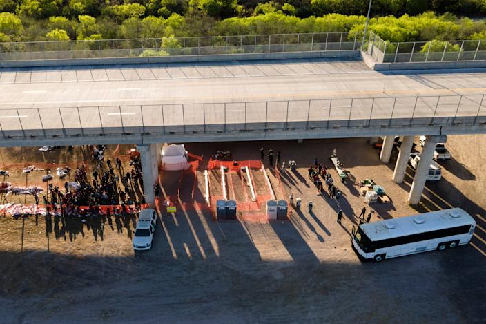 In this photo taken by a drone, migrants are seen in custody at a U.S. Customs and Border Protection processing area under the Anzalduas International Bridge, Thursday, March 18, 2021, in Mission, Texas. A surge of migrants on the Southwest border has the Biden administration on the defensive. The head of Homeland Security acknowledged the severity of the problem Tuesday but insisted it's under control and said he won't revive a Trump-era practice of immediately expelling teens and children. (AP Photo/Julio Cortez)