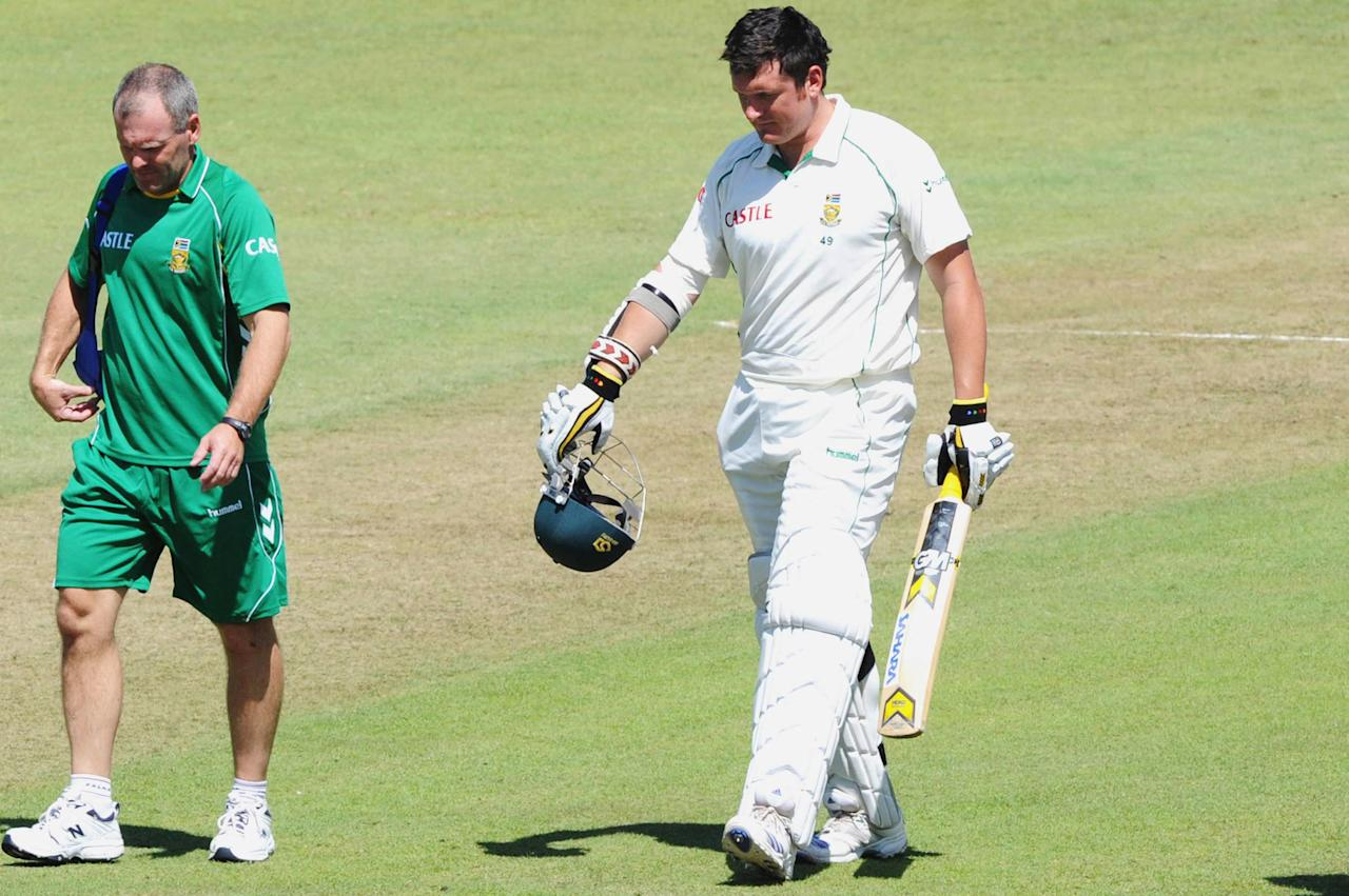 DURBAN, SOUTH AFRICA - MARCH 07:  Physiotherapist Brandon Jackson walks with Graeme Smith of South Africa as he leaves the field retiring hurt after being struck by a delivery from Mitch Johnson of Australia during day two of the Second Test between South Africa and Australia played at Kingsmead on March 7, 2009 in Durban, South Africa.  (Photo by Lee Warren/Gallo Images/Getty Images)