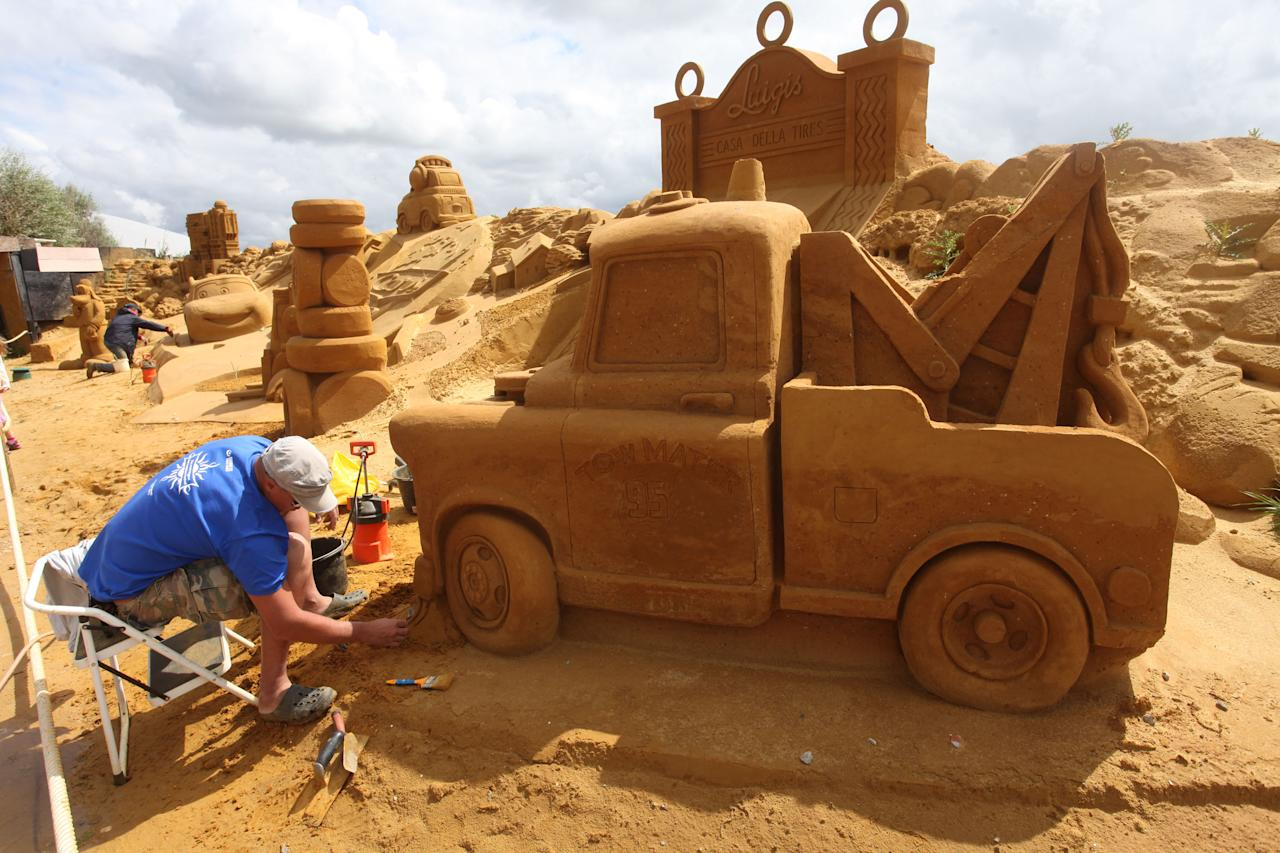 BLANKENBERGE, BELGIUM - JULY 22: A sand sculpture artist works during the Sand Sculpture Festival with Sand Sculptures based on the Magical Moments Festival of Disneyland Paris on July 22, 2011 in Blankenberge, Belgium. (Photo by Mark Renders/Getty Images)
