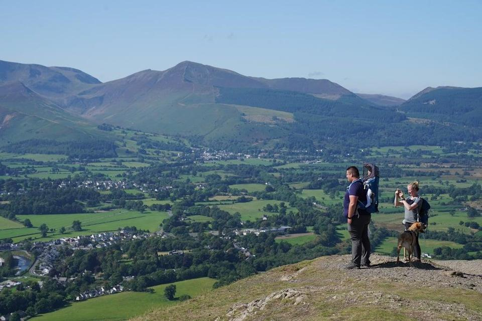 Walkers take in the view of Keswick in Cumbria (Owen Humphreys/PA) (PA Wire)