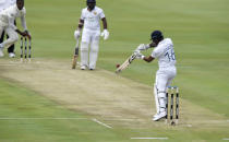 Sri Lanka's Dimuth Karunaratne, centre, plays a shot on day one of the first cricket test match between South Africa and Sri Lanka at Super Sport Park Stadium in Pretoria, South Africa, Saturday, Dec. 26, 2020. (AP Photo/Catherine Kotze)