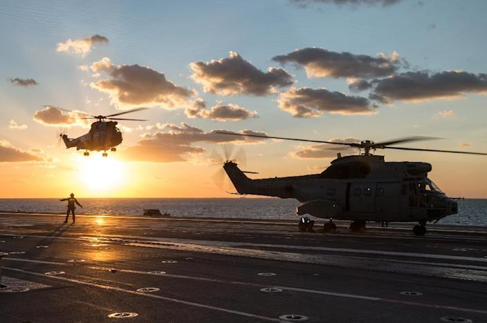 """French helicopters land on the aircraft carrier Charles de Gaulle in the eastern Mediterranean Sea French President Francois Hollande is expected to give a speech to the crew of the carrier which is off the coast of Syria, three weeks after he declared """"war"""" on the jihadists after attacks on Paris in which 130 were killed. (AFP Photo/Christian Carvallo)"""