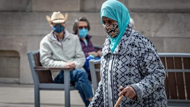 A woman walks down Bank Street while two people sit on a nearby bench on April 27, 2021, during the COVID-19 pandemic. (Brian Morris/CBC - image credit)