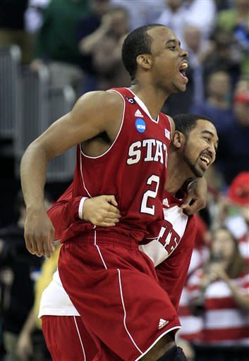 North Carolina State's Lorenzo Brown (2) celebrates with a teammate after NC State defeats Georgetown 66-63 in an NCAA men's college basketball tournament third-round game in Columbus, Ohio, Sunday, March 18, 2012. (AP Photo/Tony Dejak)