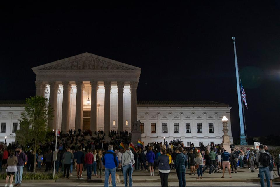 The national flag flies at half staff as people gather to mourn the passing of Supreme Court Justice Ruth Bader Ginsburg at the steps in front of the Supreme Court. Source: Getty