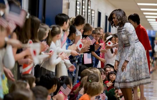 "<p>Fittingly enough, to visit Great Falls Elementary School in Great Falls, Virginia, Obama chose a floral and lace dress from Japanese-born Los Angeles-based Tadashi Shoji's <a href=""http://www.style.com/slideshows/fashion-shows/spring-2015-ready-to-wear/tadashi-shoji/collection/27"" rel=""nofollow noopener"" target=""_blank"" data-ylk=""slk:Spring 2015 Ready-to-Wear collection"" class=""link rapid-noclick-resp"">Spring 2015 Ready-to-Wear collection</a>. <br></p>"