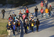 Migrants who aim to reach the U.S. walk along a highway as they leave San Pedro Sula, Honduras, early Tuesday, March 30, 2021. (AP Photo/Delmer Martinez)