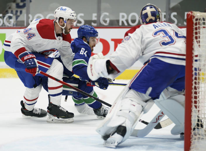 Montreal Canadiens defenseman Joel Edmundson (44) checks Vancouver Canucks centre Tyler Motte (64) in front of Canadiens goaltender Jake Allen (34) during the second period of an NHL hockey game Thursday, Jan. 21, 2021, in Vancouver, British Columbia. (Jonathan Hayward/The Canadian Press via AP)