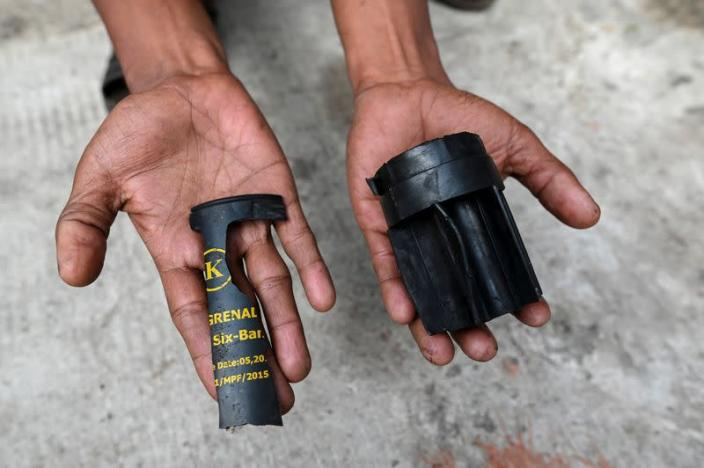 A man holds parts of a teargas grenade that riot police officers used to disperse a crowd that held a protest the night before in Yangon's Tamwe neighborhood