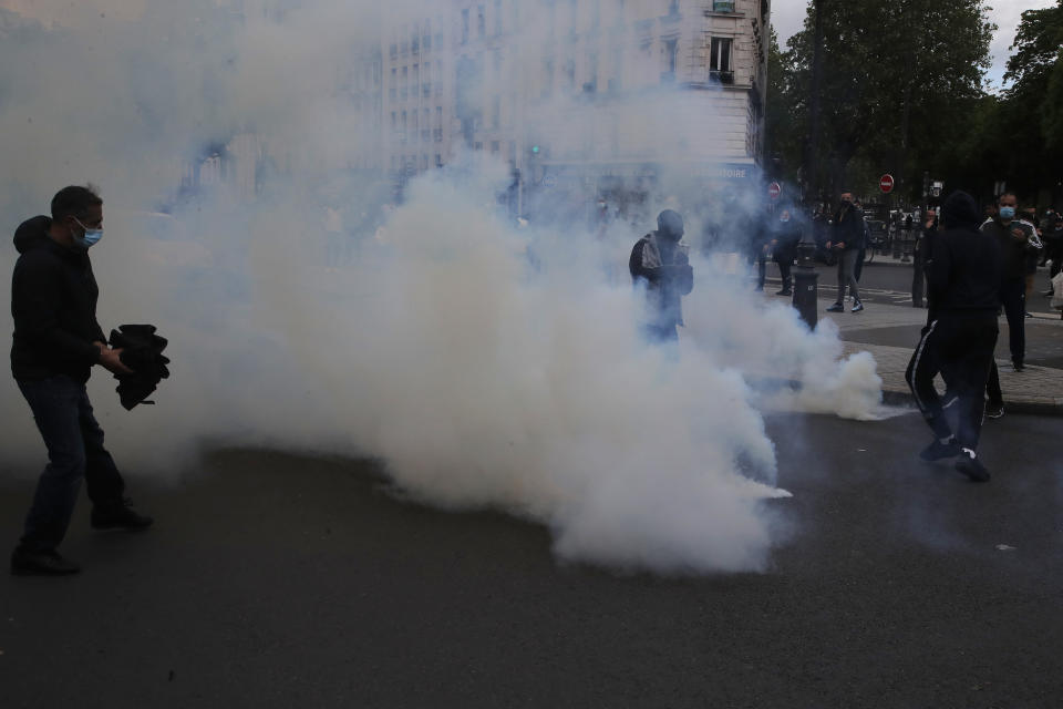 Demonstrators walk through tear gas grenades fired by police forces during a banned protest in support of Palestinians in the Gaza Strip, Saturday, May, 15, 2021 in Paris. Marches in support of Palestinians in the Gaza Strip were being held Saturday in a dozen French cities, but the focus was on Paris, where riot police got ready as organizers said they would defy a ban on the protest. (AP Photo/Michel Euler)