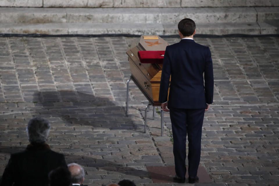 French President Emmanuel Macron pays his respects by the coffin of slain teacher Samuel Paty in the courtyard of the Sorbonne university during a national memorial event, Wednesday, Oct. 21, 2020 in Paris. French history teacher Samuel Paty was beheaded in Conflans-Sainte-Honorine, northwest of Paris, by a 18-year-old Moscow-born Chechen refugee, who was later shot dead by police. (AP Photo/Francois Mori, Pool)