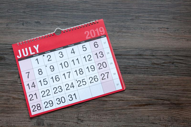 A red calendar, lying on top of a wooden table top, turned to the month of July.
