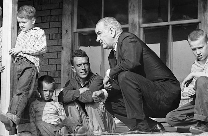 President Lyndon Johnson listens to Tom Fletcher, father of eight, describe some of the problems facing the residents of Inez, Kentucky, in April 1964. (Photo: Bettmann Archive/Getty Images)