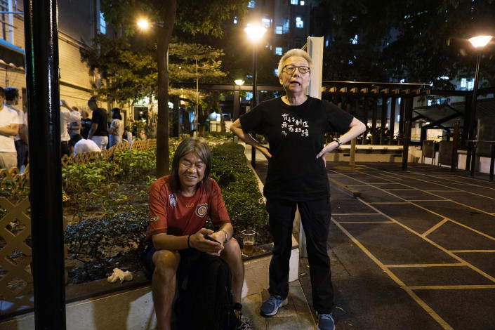 In this Oct. 9, 2020 photo, Grace Ma, right, chats with pro-democracy activist Leung Kwok-hung outside her bar Club 71 in Hong Kong. The bar known as a gathering place for pro-democracy activists and intellectuals is closing. For years, the storied bar has served as a watering hole for the city's pro-democracy activists and intellectuals, who could freely engage in discussions over a round of beer or two. (AP Photo/Kin Cheung)