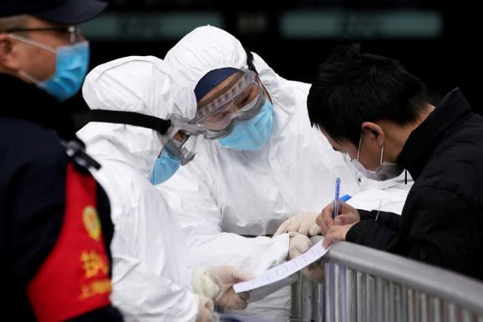 Staff members wearing protective masks check a passenger at Shanghai railway station in Shanghai