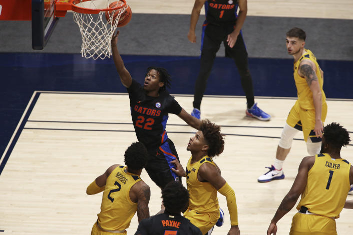 Florida guard Tyree Appleby (22) shoots while defended by West Virginia forward Jalen Bridges (2) and guard Miles McBride (4) during the second half of an NCAA college basketball game Saturday, Jan. 30, 2021, in Morgantown, W.Va. (AP Photo/Kathleen Batten)