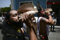 Activists blow on a conch shell during a march demanding statues and street names commemorating symbols of colonial oppression be removed, in San Juan, Puerto Rico, Saturday, July 11, 2020. Dozens of activists marched through the historic part of Puerto Rico's capital on Saturday to demand that the U.S. territory's government start by removing statues, including those of explorer Christopher Columbus. (AP Photo/Carlos Giusti)
