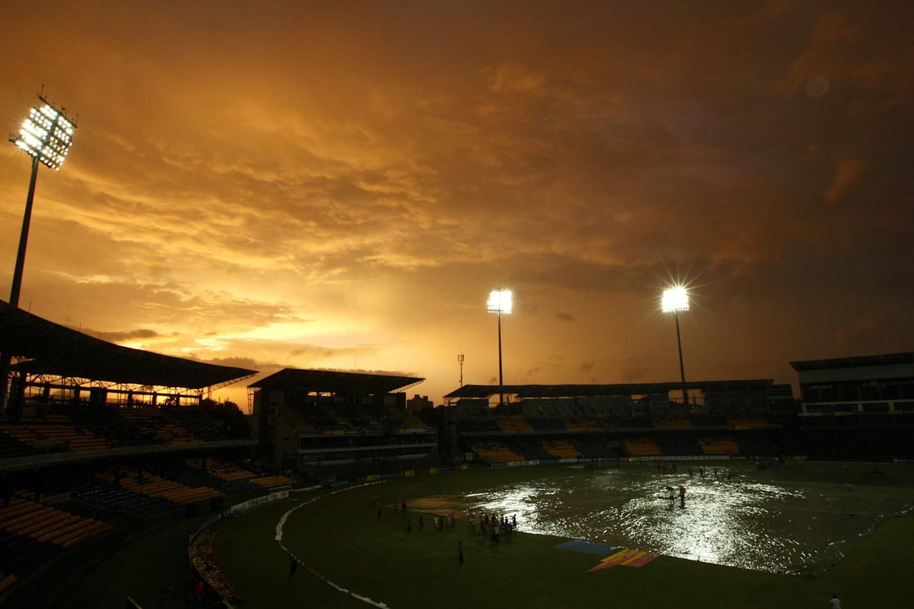 COLOMBO, SRI LANKA - JUNE 13:  Ground workers pull the rain covers over the field after rain stopped play during the third one day international match between Sri Lanka and Pakistan at R. Premadasa Stadium on June 13, 2012 in Colombo, Sri Lanka.  (Photo by Buddhika Weerasinghe/Getty Images)