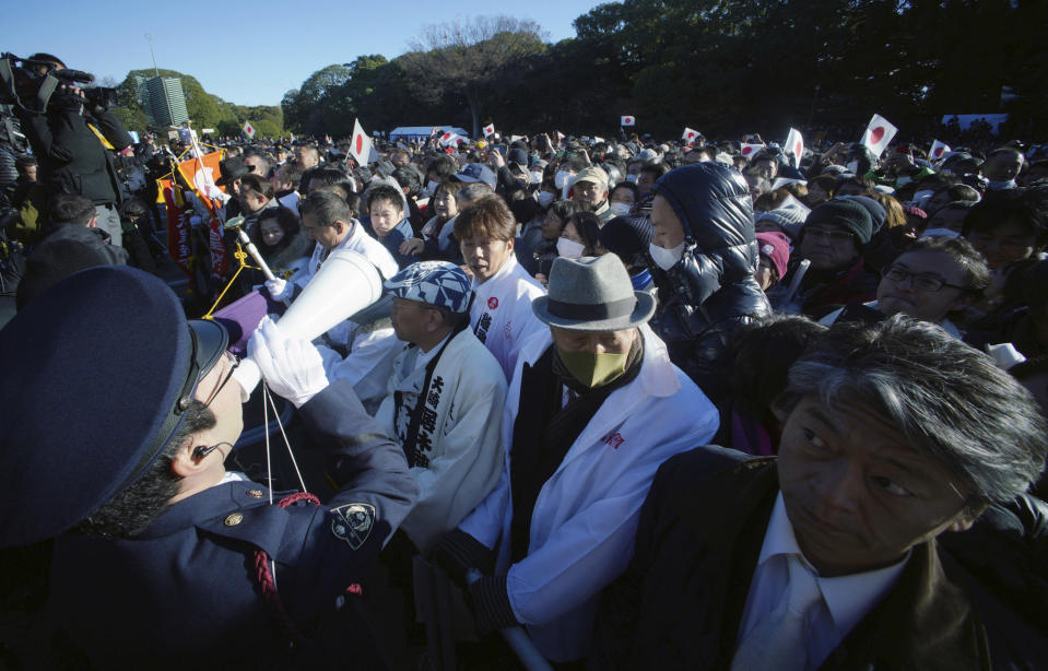 Well-wishers wait for Japan's Emperor Akihito's public appearance with his family members at Imperial Palace during his New Year's public appearance with his family members at Imperial Palace in Tokyo Wednesday, Jan. 2, 2019. (AP Photo/Eugene Hoshiko)