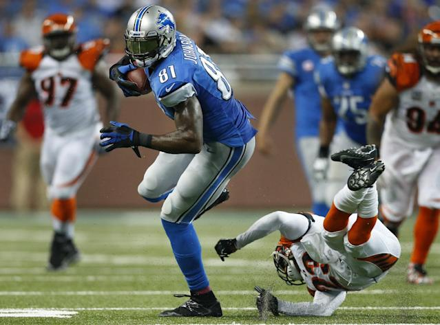 Detroit Lions wide receiver Calvin Johnson (81) avoids the tackle of Cincinnati Bengals cornerback Terence Newman (23) in the first quarter of an NFL football game against Sunday, Oct. 20, 2013, in Detroit. (AP Photo/Rick Osentoski)