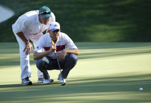 Spain's Sergio Garcia and his caddie Neill Wallace (rear) line up a putt on the 13th green during the first round of the Masters golf tournament at the Augusta National Golf Club in Augusta, Georgia April 10, 2014. REUTERS/Mike Blake (UNITED STATES - Tags: SPORT GOLF)