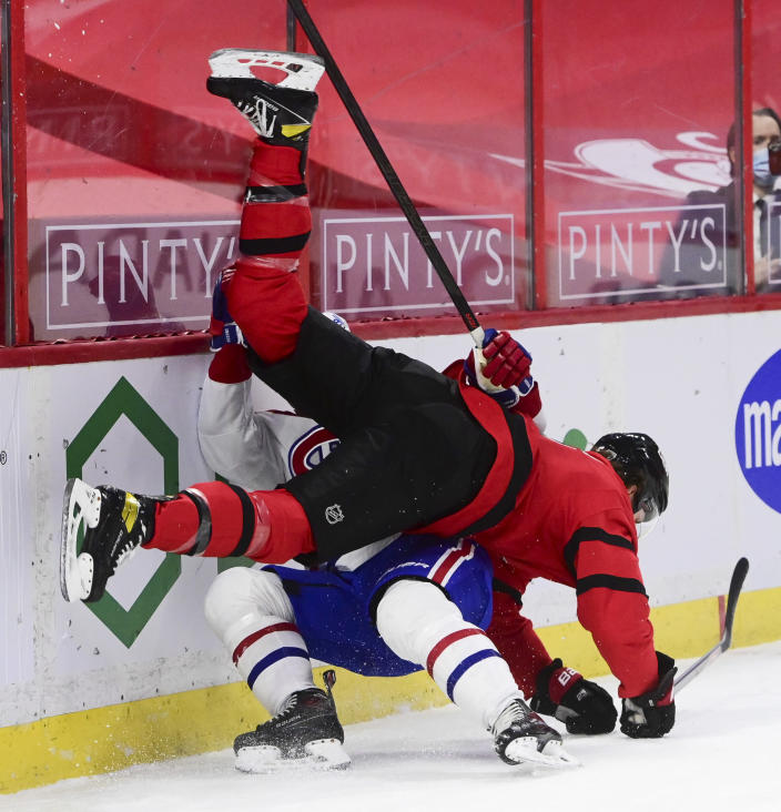 Montreal Canadiens center Nick Suzuki (14) and Ottawa Senators defenseman Mike Reilly (5) crash into the boards during the first period of an NHL hockey game in Ottawa on Saturday, Feb. 6, 2021. (Sean Kilpatrick/The Canadian Press via AP)